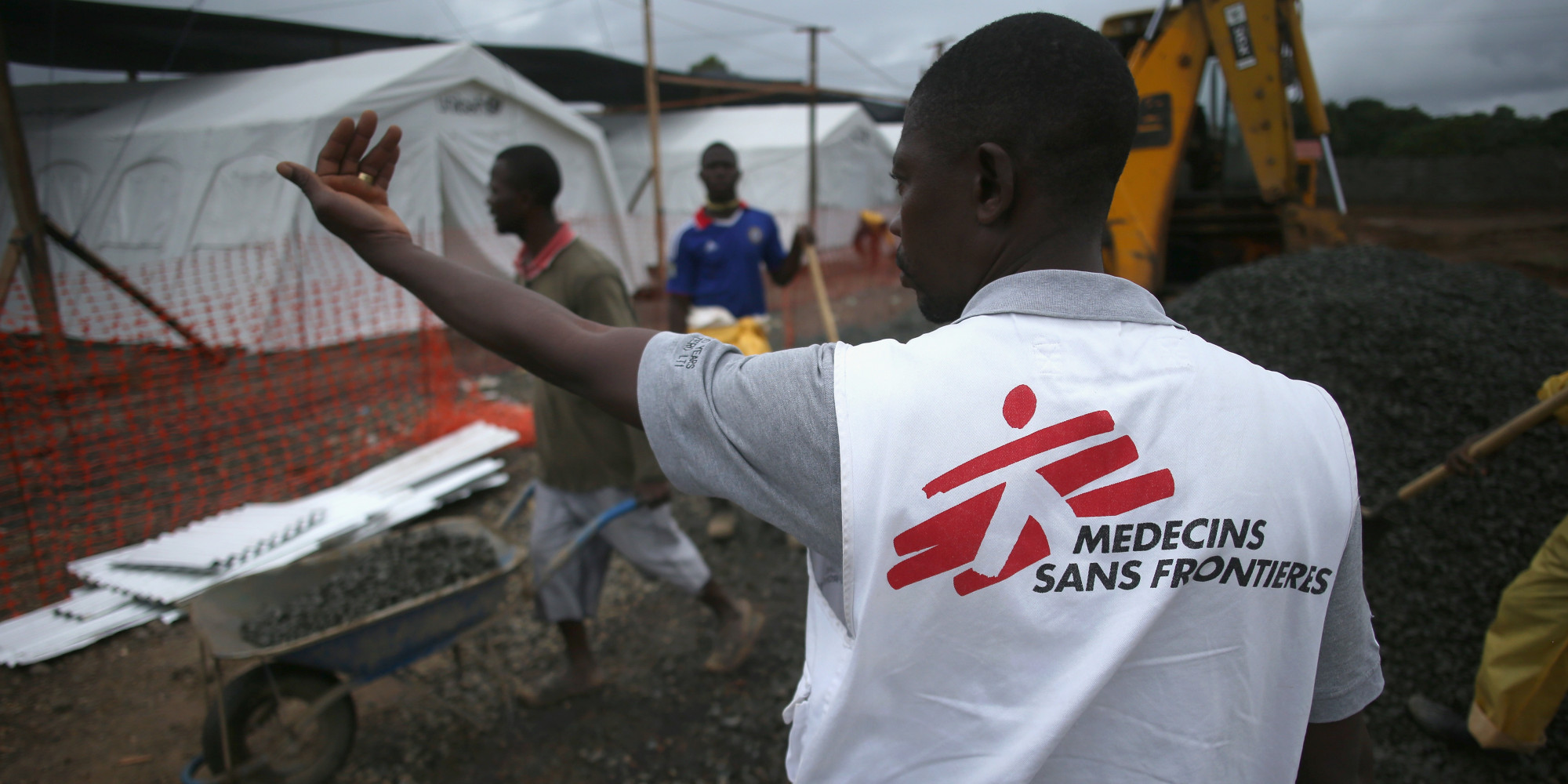 MONROVIA, LIBERIA - AUGUST 17:  A Doctors Without Borders (MSF), staffer supervises as construction workers complete the new MSF Ebola treatment center on August 17, 2014 near Monrovia, Liberia. The facility initially has 120 beds, making it the largest such center for Ebola treatment and isolation in history and MSF plans to expand it to a 350-bed capacity. Tents, beds and much of the medical supplies at the center were provided by UNICEF. The virus has killed more than 1,000 people in four African countries, and Liberia now has had more deaths than any other country.  (Photo by John Moore/Getty Images)