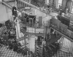 Hall du réacteur NRX – le cœur se trouve dans la structure cylindrique centrale. Les expériences étaient concentrées autour des fenêtres de sortie de faisceaux. (Photo: domaine public)