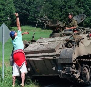 Près de la barricade de Kanesatake, un Métis dépose une plume dans le canon d'un tank de l'armée. (Photo : PC/Bill Grimshaw)