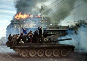 Romanian demonstrators sit on top of a tank as it passes in front of a burning building, December 22 1989, in Bucharest during the 1989 anti-communist revolution. (Photo: Radu Sigheti)
