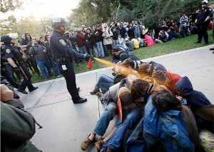 En maintenant une attitude non-violente stratégique, ces manifestants d'Occupy impose un dilemme à l'officier par la démonstration  des différences de valeurs, 18 novembre 2011. (Photo: inconnu)